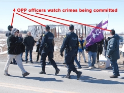 March 27/11: 4 OPP officers watch DCE occupiers destroy our Truth & Reconciliation/Apology monument, and then insert Six Nations flags in the side of the base before buring the monument and our Canadian flag.