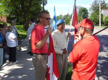 Day 11 of 'Blue Beret' vigil outside London (Ontario, Canada) Muslim Mosque organized by former peacekeeper Mark Vandermaas (not visible); Stuart Laughton of Never Again Group (wearing red shirt, holding Canadian flag) talks to Al Gretzky, Director of Communications for the Canadian chapter of the International Free Press Society while another former peacekeeper, Merlyn Kinrade of Caledonia looks on. July 03/11