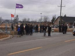 120127 OPP wait for Caledonia Eight & supporters while Mohawk Warrior and Six Nations flags fly behind them.
